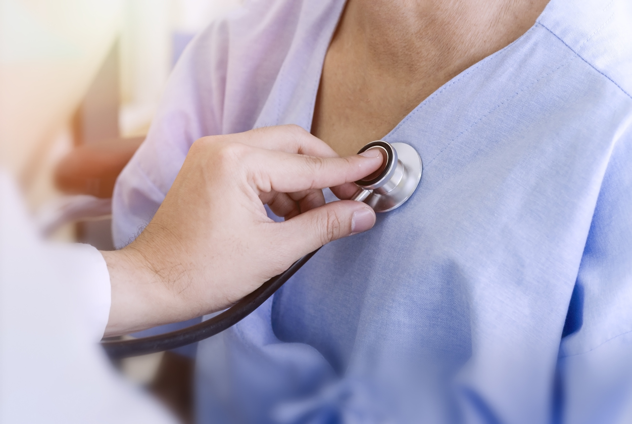 healthy concept; Doctor checking patient's heart with stethoscope at a hospital