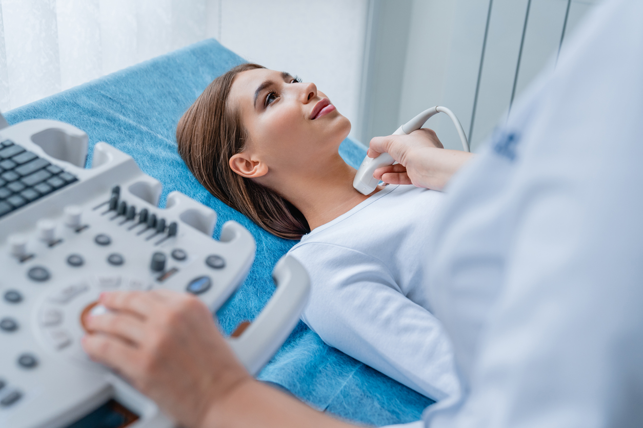 Woman getting her neck examined by female doctor using ultrasound scanner at modern clinic